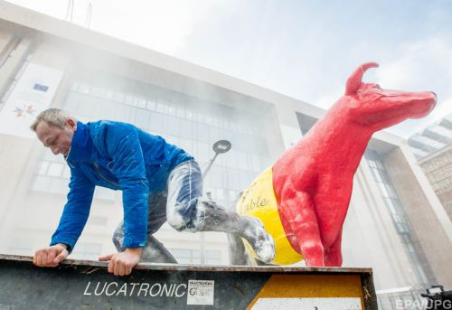 European Milk board (EMB) representatives spray milk powder in front of the EU Council headquarters
