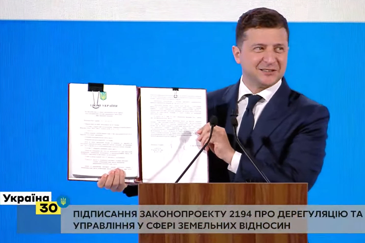 President of Ukraine Volodymyr Zelenskyy holding the newly signed law On Amending the Land Code of Ukraine and Other Laws on Improving Administration System and Land Relation Deregulation